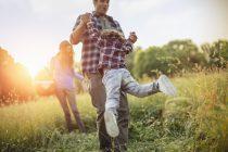 Padre levantando en brazos a su hizo en el campo y disrutando de la naturaleza