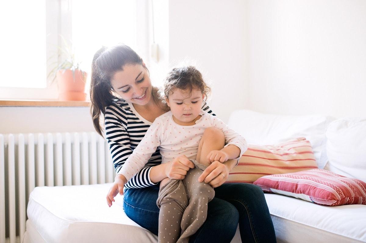 Madre e hija delante de radiador, confort gas natural
